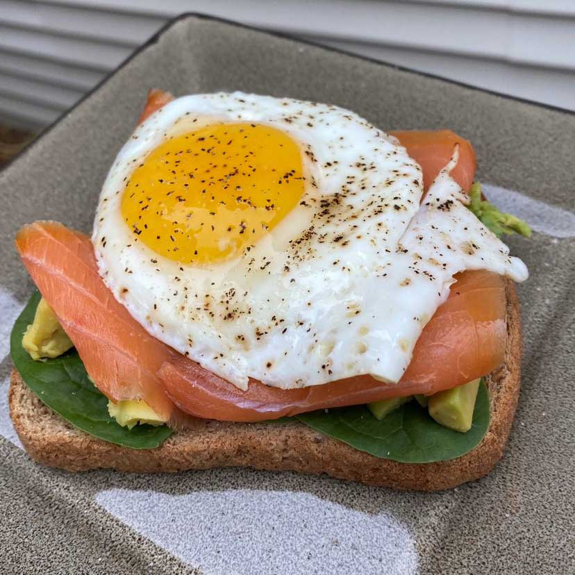 Avocado toast with salmon and an egg