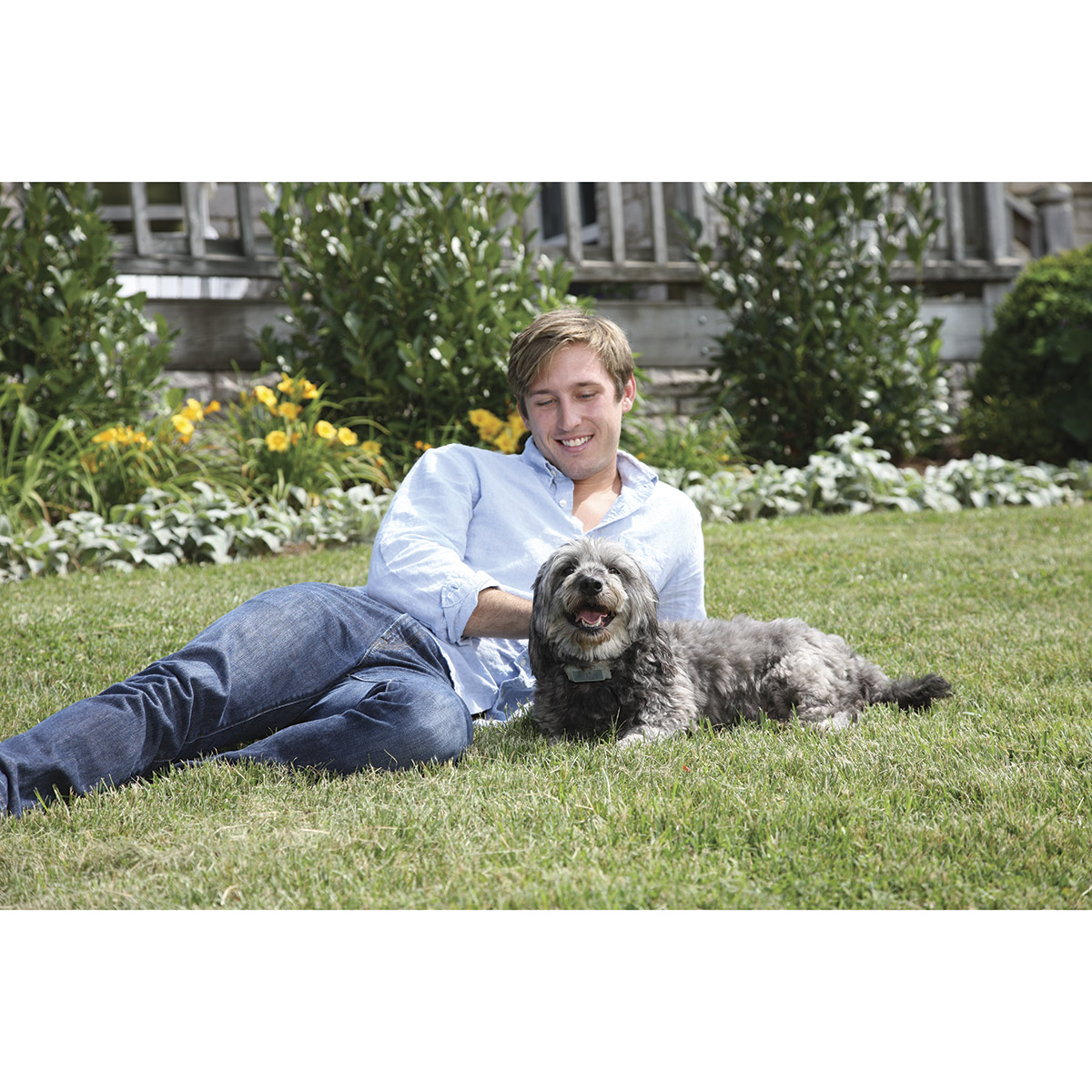 Man laying on Grass with PetSafe Ultrasonic Bark Control Collar on Dog - Both look happy