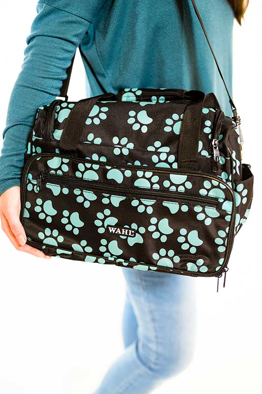 Woman toting Wahl Travel Paw Print Bag Turquoise for Groomers
